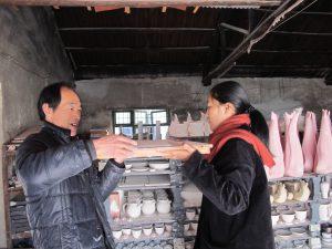 De 'kilnman' en 'pottery workshop assistent Snow' schuiven samen kleiplaat voor lunchproject in de 'public kiln'